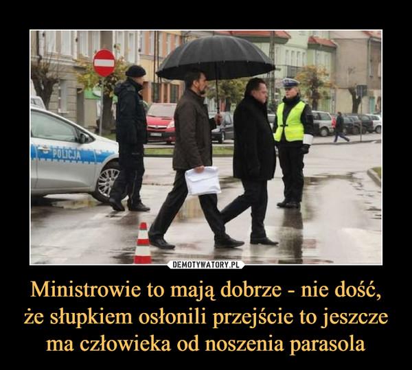 Ministrowie to mają dobrze - nie dość, że słupkiem osłonili przejście to jeszcze ma człowieka od noszenia parasola –